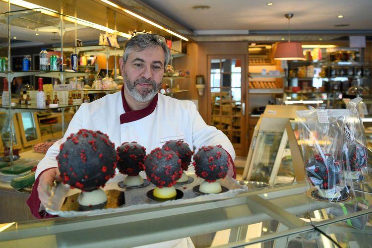 Chocolatier Jean-Francois Pre menyiapkan telur paskah berbentuk seperti virus corona di tokonya di Landivisiau, Barat Perancis, 7 Maret 2020. Cokelat ini terbuat dari cokelat putih yang diberikan pewarna hitam serta dipadukan dengan kacang almond yang diwarnai merah.