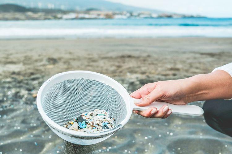 Ilustrasi mikroplastik di pantai yang mencemari laut. Dampak sampah plastik di lautan.