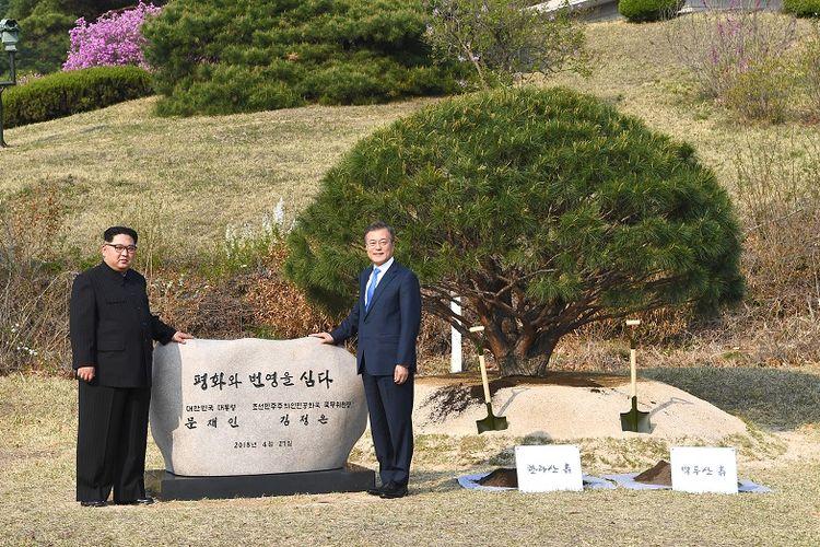 Pemimpin Korea Utara Kim Jong Un (kiri) and Presiden Korea Selatan Moon Jae-in (R) berpose di depan sebuah prasasti bertuliskan Perdamaian dan Kemakmuran sedang Ditanam setelah keduanya menanam sebatang pohon di dekat garis demarkasi yang membagi kedua negara, Jumat (27/4/2018).