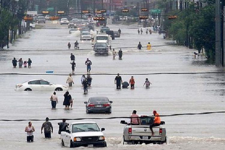 Warga berjalan di tengah banjir yang menggenangi jalan raya Telephone di kota Houston, Amerika Serikat, Minggu (27/8/2017) waktu setempa.