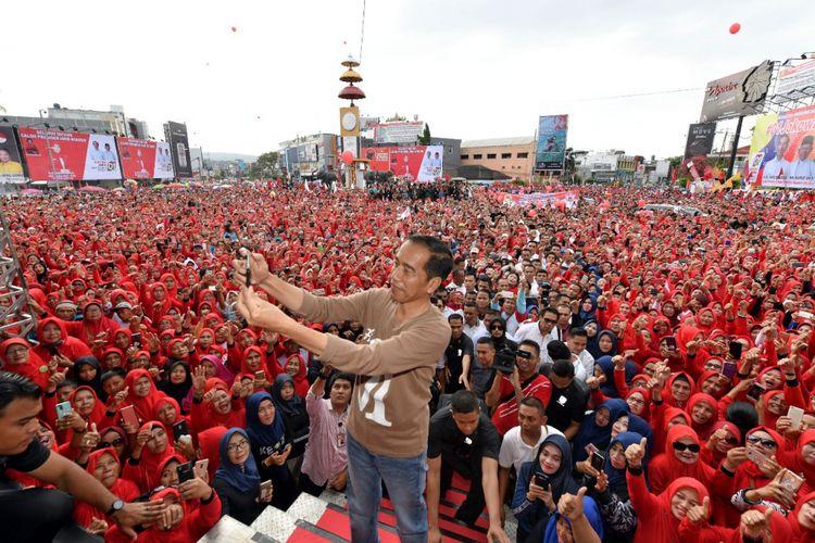 Calon presiden nomor urut 1 Joko Widodo saat berswafoto dengan latar belakang lautan massa di acara gerak jalan sehat di pusat kota Bandar Lampung, Sabtu (24/11/2018).