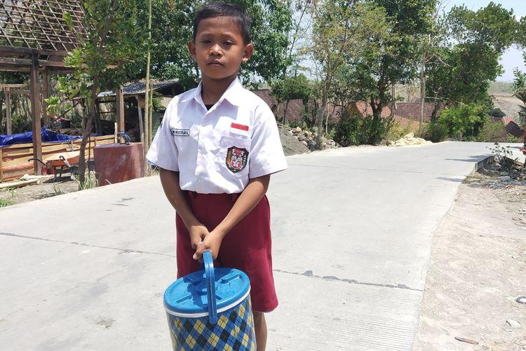 Tegoh Niccolas Saputra (10), siswa kelas 4 SD Negeri 3 Banyurip, Kecamatan Jenar, Sragen, Jawa Tengah membawa termos berisi es kucir untuk dijual di sekolah.