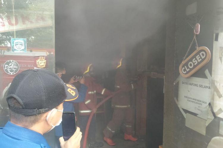 Petugas pemadam kebakaran saat melokalisir titik api di sebuah toko yang menjual rokok elektronik yang berada di Sukarasa, Kecamatan Tangerang, Kota Tangerang, Selasa (6/4/2021).