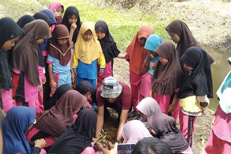 Seorang Relawan Kanti Sungai saat mengajarkan anak-anak untuk menanam pohon di bibir kanal