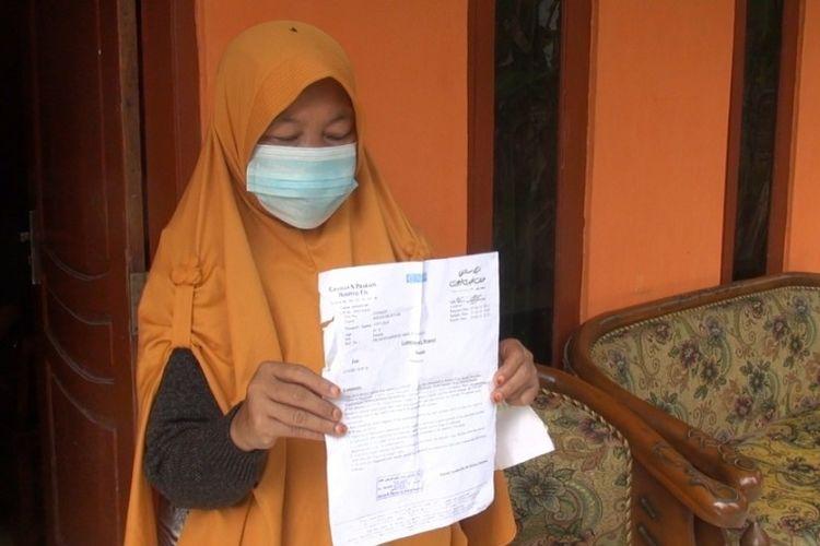 Aisyah (46) menunjukan hasil swab PCR yang menunjukan hasil negatif Covid-19 saat di kediamannya di Desa Kubangjati, Jatibarang, Brebes, Jumat (5/3/2021) (istimewa)