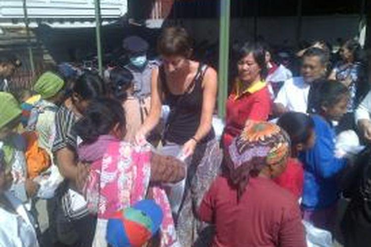 Wisatawan asal Swiss, Andre, membantu membagikan sembako dalam acara sedekah bumi yang diadakan oleh Yayasan Kelenteng Eng An Kiong, Kota Malang, Jawa Timur, Rabu (21/8/2013).