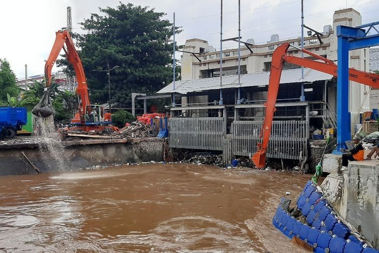 Dua unit alat pengeruk beroperasi mengangkut sampah yang tertahan di Pintu Air Manggarai, Kamis (2/1/2019).(KOMPAS.com/Ardito Ramadhan D)