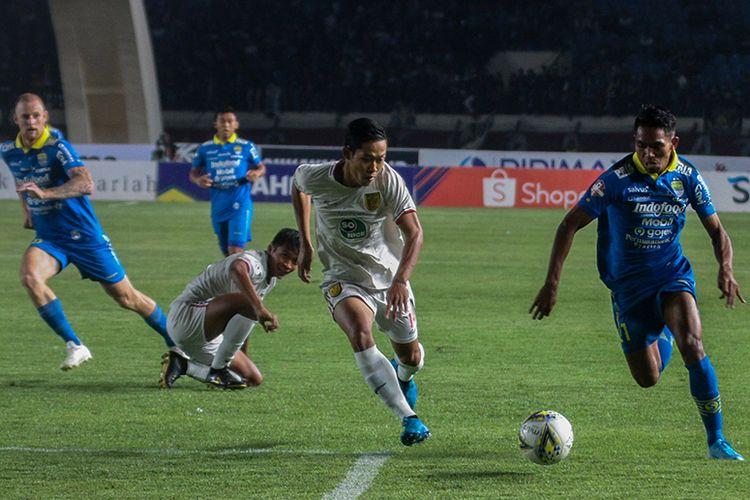 Winger Persib Bandung, Frets Butuan (biru) mencoba melewati hadangan pemain belakang Persela Lamongan, saat kedua tim bersua pada pekan ke-30 Liga 1 2019, di Stadion Si Jalak Harupat, Selasa (3/12/2019).