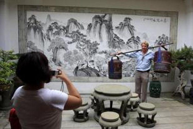 Wisatawan mengabadikan kunjungan mereka di salah satu rumah milik warga China peranakan di kawasan George Town, Penang, Malaysia, Rabu (28/10/2009).