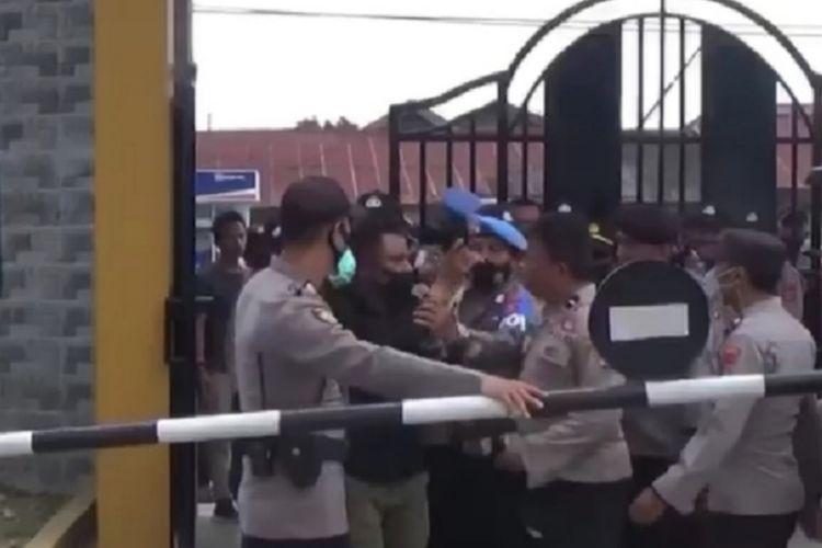 Rudinan, baju hitam, jurnalis harian berita kota Kendari menunjukkan id card nya kepada polisi sebelum mengalami penganiayaan oknum polisi saat meliput di kantor BLK Kendari ( Istimewa)
