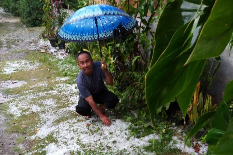 Suprihono (42), warga Kampung Paya Tungel, Kecamatan Jagong Jeget, Kabupaten Aceh Tengah saat menunjukan hujan es yang terjadi pada Minggu (7/7/2019) siang di halaman rumahnya.