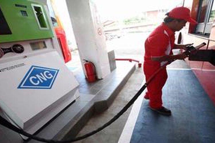 Petugas mengisi bahan bakar gas (BBG) jenis gas alam terkompresi (compresed natural gas/CNG) ke bus Transjakarta