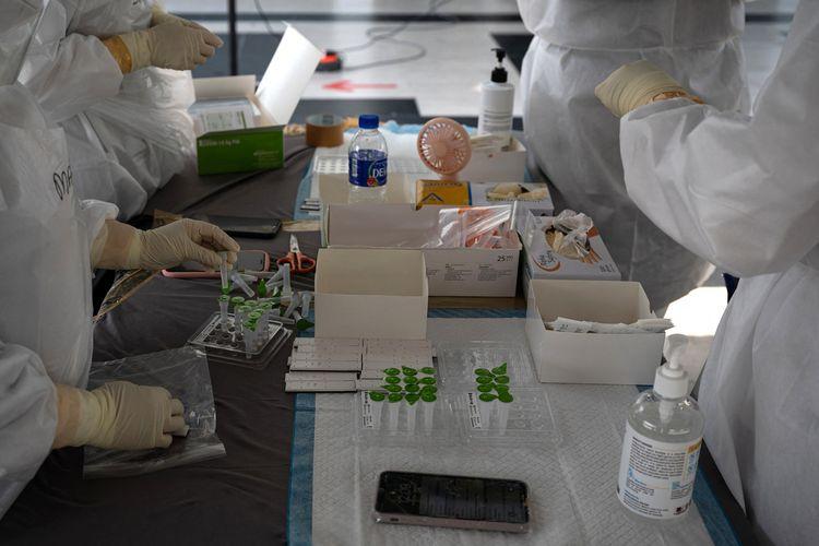 Tenaga kesehatan dengan memakai APD menyiapkan alat tes Covid-19 di Shah Alam, pinggiran Kuala Lumpur, pada 17 Februari 2021.