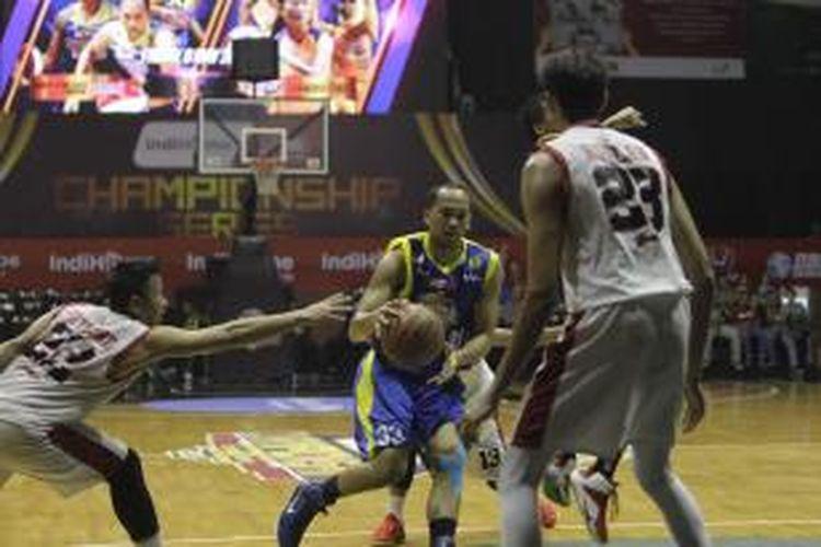 Pemain Satria Muda Britama, Arki Dikania Wisnu (tengah), mencoba menerobos pertahanan tim Stadium Jakarta saat bertemu pada semiifnal National Basketball League (NBL) di Hall Basket Gelora Bung Karno, Senayan, Jakarta, Kamis (7/5/2015).