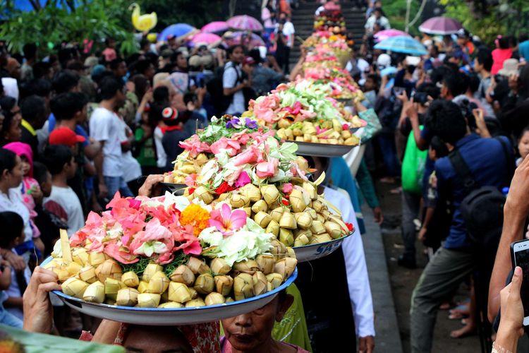 Iring iringan warga yang membawa berbagai jenis makanan dan hasil bumi di Pura Lingsar, Lombok Barat, Rabu (11/12/2019). Mereka berkeliling sebanyak 7 kali mengelilingi bangunan kemalik,sebuah bangunan yang dikeramatkan umat Hindu maupun Islam (muslim) di Lombok.