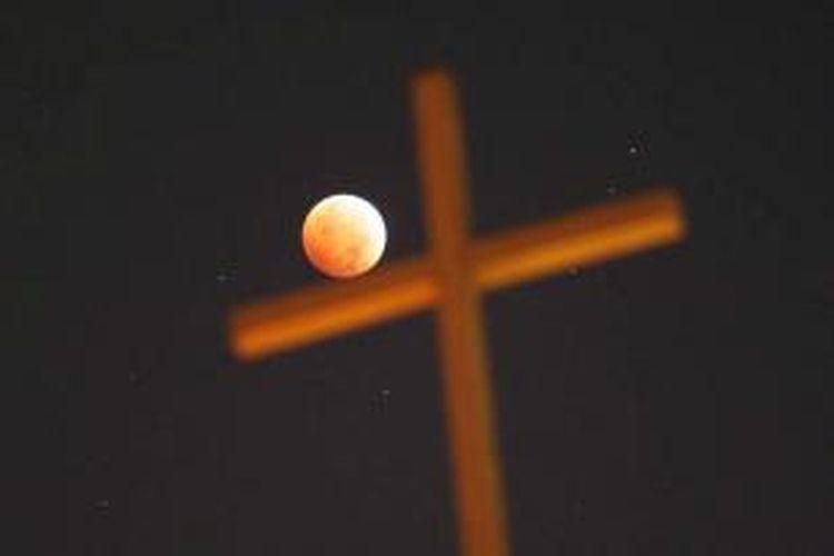 Gerhana bulan dengan latar depan salib di Los Angeles, California, 8 Oktober 2014. Warna merah pada gerhana bulan dipengaruhi oleh pembiasan atmosfer Bumi, disebut dengan 'bulan merah darah'.