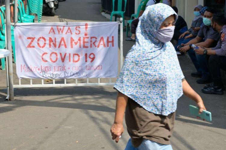 Seorang berjalan di lingkungan yang menjadi zona merah Covid-19 di Jakarta