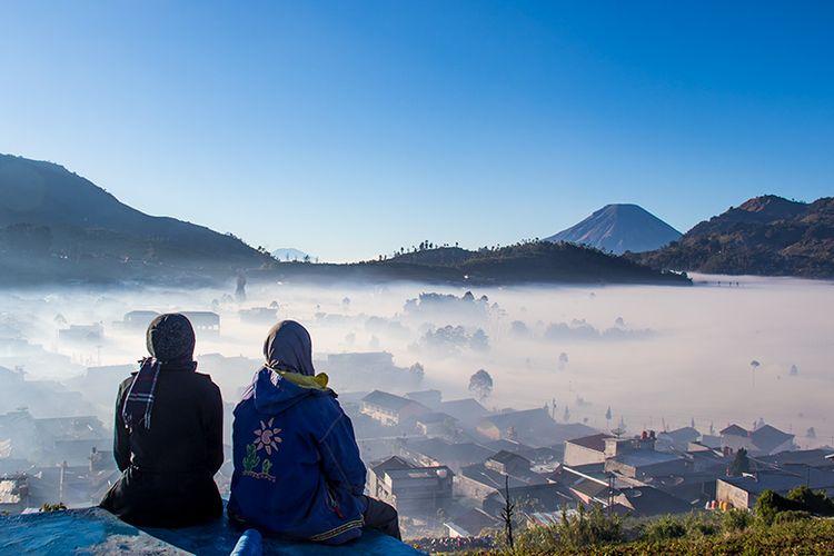 Dua wanita menikmati keindahan Dataran Tinggi Dieng yang berselimut kabut.