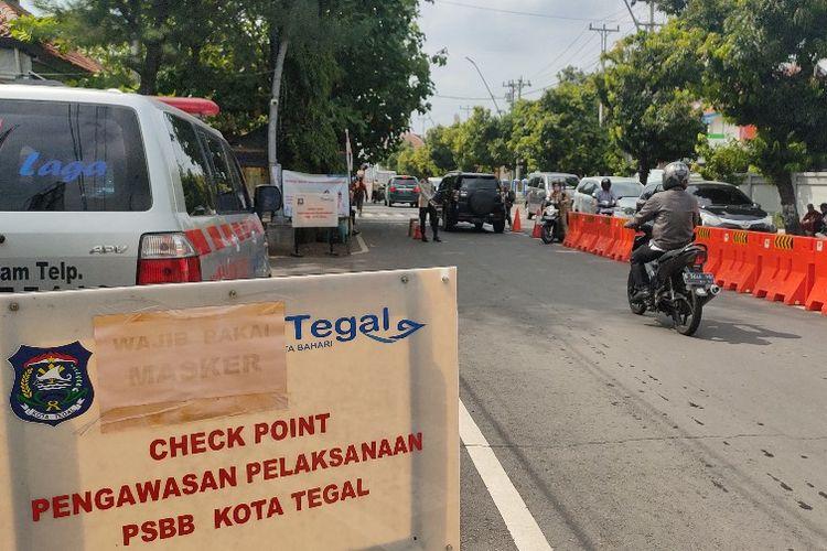 Pengendara sepeda motor melintasi posko check point pemeriksaan kesehatan di Jalan Proklamasi, Kota Tegal, saat peberlakukan PSBB, Selasa (12/5/2020).