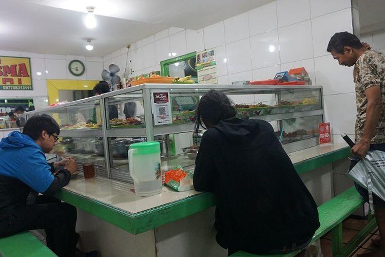 Beberapa pembeli terlihat sedang memilih dan menyantap makanan di warteg Kharisma Bahari di jalan Haji Batong Raya, kelurahan Cilandak Barat, Jakarta Selatan, Selasa (23/10/2018).