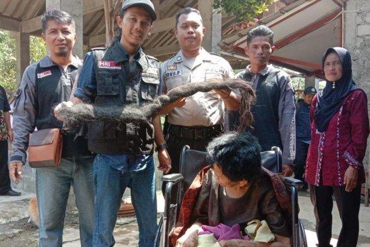 Ardian Kurniawan Santosa (bertopi) memegang rambut gimbal Mbah Iyah. (Tribun Jambi/Istimewa)
