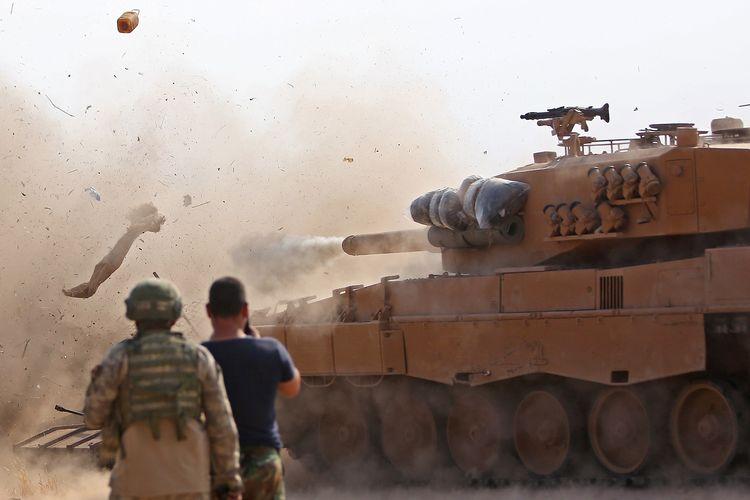Tentara Turki di kota Suriah Ras al-Ain memperhatikan ketika tank menembak di posisi yang dihuni milisi dari Pasukan Demokratik Suriah (SDF) dengan Kurdi sebagai tulang punggungnya pada 28 Oktober 2019. Militer Turki dan Suriah dilaporkan terlibat baku tembak di perbatasan, dengan enam tentara Suriah tewas.