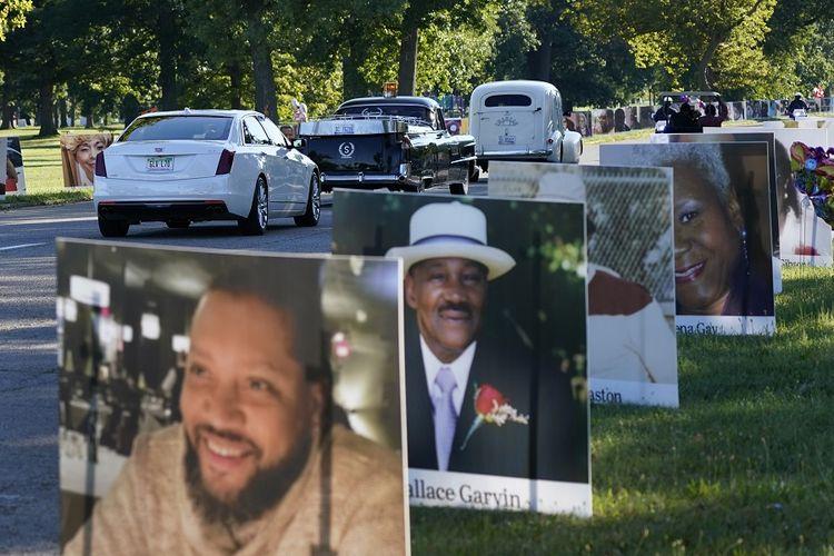 Kendaraan melewati foto-foto korban Covid-19, Senin (31/8/2020) di Belle Isle di Detroit, Michigan, Amerika Serikat (AS).