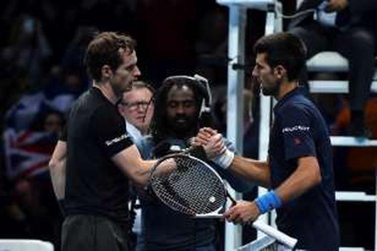 Petenis Inggris Raya, Andy Murray (kiri), bersalaman dengan petenis Serbia, Novak Djokovic, setelah menyelesaikan laga final ATP World Tour Finals di London, Inggris, Minggu (20/11/2016).