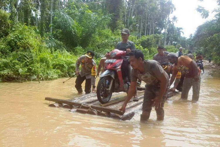 Polisi membantu warga melewati banjir di Desa Pante Labu, Kecamatan Pante Bidari, Kabupaten Aceh Timur terendam banjir, Senin (19/11/2018).