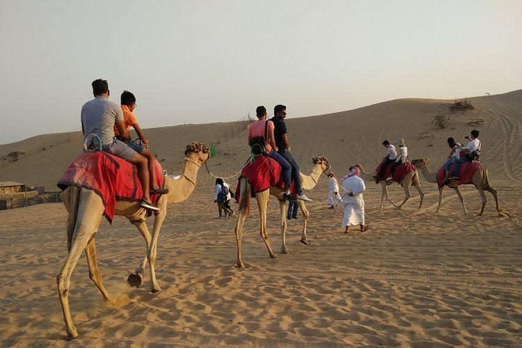 Wisatawan sedang naik unta di kawasan gurun pasir di Dubai, Uni Emirate Arab, Selasa (31/10/2017). Menjelajah gurun pasir adalah salah satu atraksi wisata yang bisa dilakukan saat berlibur ke Dubai.