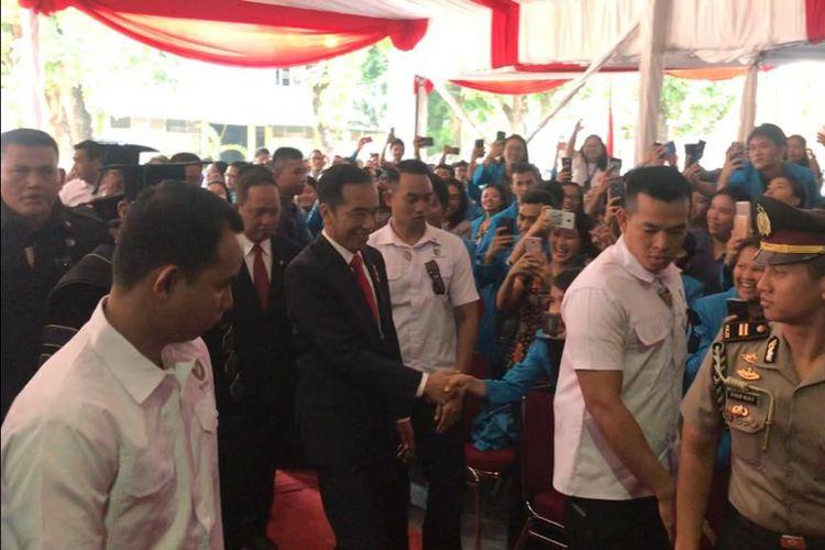 Presiden Joko Widodo saat menghadiri Sidang Terbuka Senat UKI dalam rangka Lustrum ke-13 UKI di Lapangan Bola UKI, Jakarta Timur, Senin (15/10/2018).