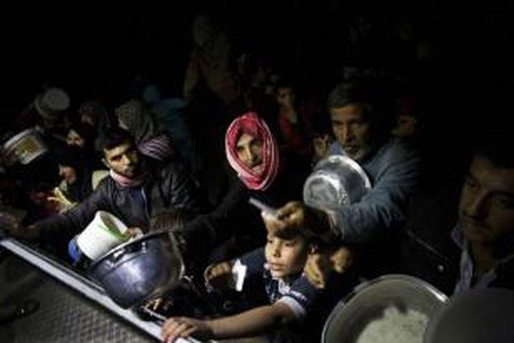 FILE - Pengungsi Suriah antre makanan di sebuah dapur umum sebuah LSm di kamp pengungsi dekat Azaz, Suriah, 23 Oktober 2012. Foto ini salah satu dari 20 foto karya fotografer AP yang memenangkan Pulitzer Prize 2013 kategori foto Breaking News.