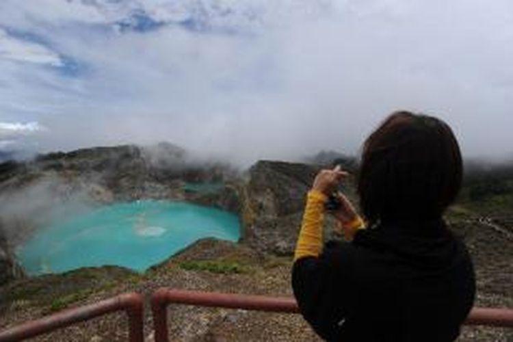 Wisatawan menikmati pesona Danau Kelimutu di Kabupaten Ende, Nusa Tenggara Timur, Minggu (8/1/2012). Danau Kelimutu yang menawarkan keindahan alamnya masih menjadi daya tarik wisatawan domestik dan mancanegara yang berkunjung ke Pulau Flores.