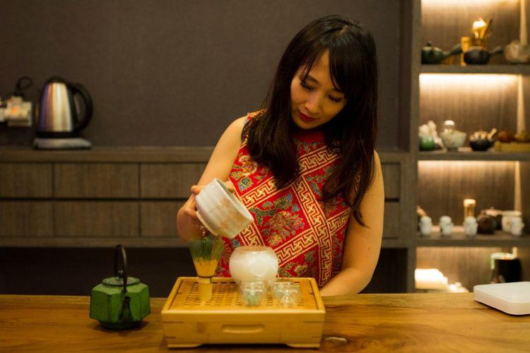 Ratna Somantri, pakar teh, tengah membuat matcha latte,