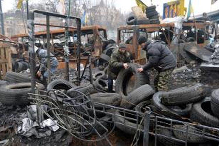 Para pengunjuk rasa antipemerintah memperbaiki barikade yang mereka bangun di salah satu sudut kota Kiev. Gambar diambil pada Senin (17/2/2014) waktu setempat.