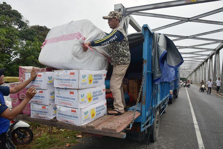 Sejumlah petugas dinas sosial menurunkan bantuan di atas jalan di lokasi banjir Kecamatan Gunung Sahilan, Kabupaten Kampar, Riau, Rabu (11/12/2019). Pemkab Kampar mulai menyalurkan bantuan obat, makanan bayi, dan makanan untuk ratusan warga terdampak banjir akibat luapan Sungai Subayang karena warga mulai mengeluhkan sakit seperti flu, hipertensi dan gatal-gatal akibat banjir yang sudah berlangsung selama tiga hari di daerah itu.