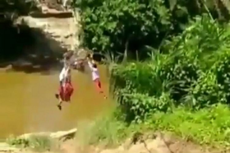 Tangkapan layar video viral tiga anak SD menyeberangi sungai dengan bergantung pada keranjang yang diikat tali di Desa Kuntu, Kecamatan Kampar Kiri, Kabupaten Kampar, Riau, Kamis (10/6/2021).