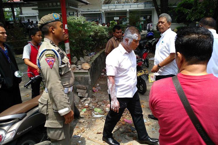 Kepala Satpol PP Kota Medan M. Sofyan dengan kepala bagian belakang, leher dan tangan kanan dilumuri sesuatu berwarna putih. Sebelumnya, dia tersiram air panas.