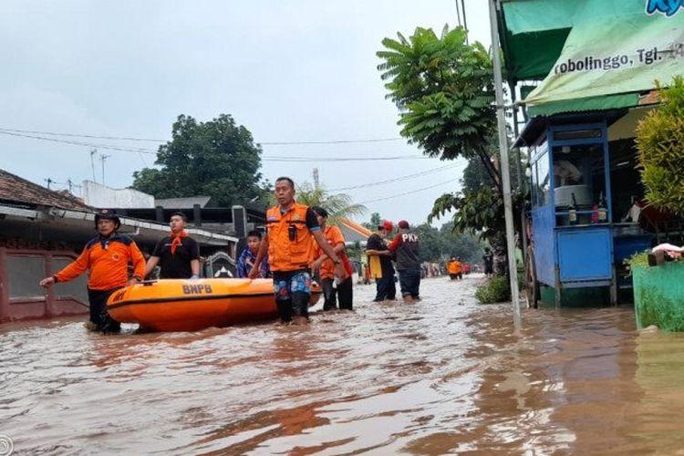 Petugas membawa perahu karet untuk mengevakuasi warga yang rentan seperti lansia, anak-anak, dan ibu hamil saat banjir menerjang Kecamatan Dringu, Kabupaten Probolinggo, Rabu (10/3/2021) petang