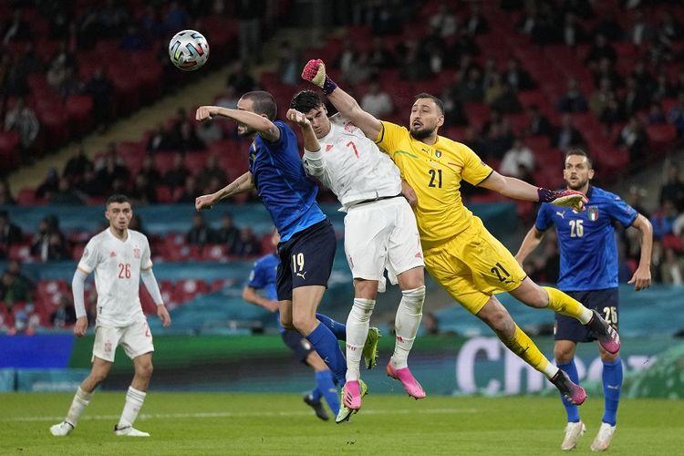 (Kiri ke kanan) bek Italia Leonardo Bonucci, penyerang Spanyol Alvaro Morata, dan penjaga gawang Italia Gianluigi Donnarumma berebut bola dalam pertandingan semifinal Euro 2020 antara Italia dan Spanyol di Stadion Wembley di London pada 6 Juli 2021.