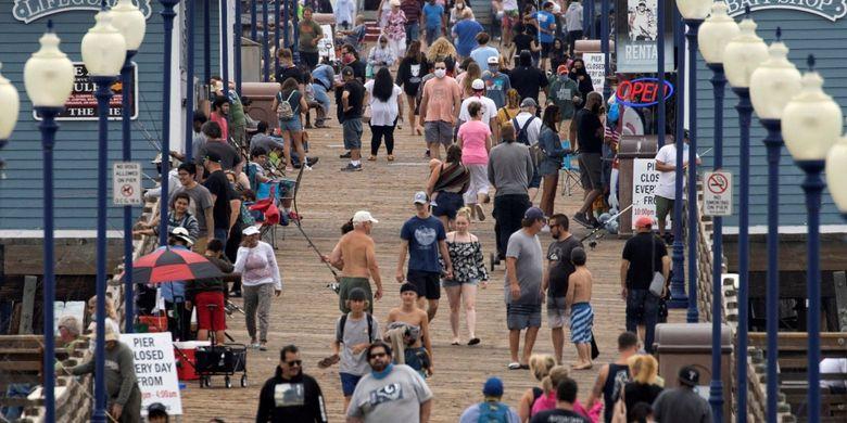Beberapa orang memakai masker saat berjalan di dermaga, ditengah pandemi virus corona (COVID-19) di Oceanside, California, Amerika Serikat, Senin (22/6/2020).