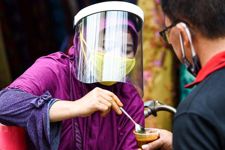 Penjual jamu keliling Tidar (kiri) dengan menggunakan masker dan pelindung wajah melayani pembeli di kawasan Pasar Baru, Jakarta, Selasa (9/6/2020). Tidar menerapkan protokol kesehatan jelang pemberlakuan protokol tatanan normal baru di Jakarta untuk tetap mencari nafkah.