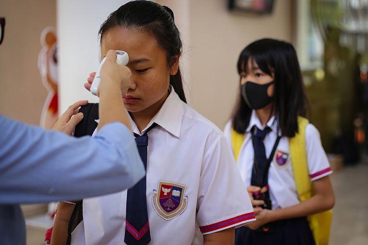 Siswa sekolah menjalani pemeriksaan suhu tubuh sebelum memasuki lingkungan sekolah di Jakarta Nanyang School, Tangerang, Banten, Rabu (4/3/2020). Pemeriksaan kondisi suhu tubuh di sekolah tersebut untuk mengantisipasi penyebaran virus menular dan siswa yang melibihi suhu lebih dari 37 derajat akan dipulangkan.
