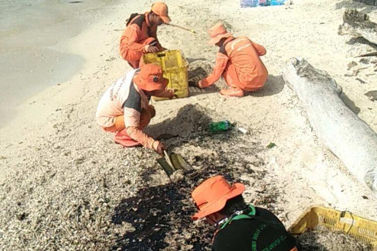 Anggota Suku Dinas Lingkungan Hidup Kepulauan Seribu membersihkan minyak dari pantai Pulau Pari, Minggu (8/4/2018).