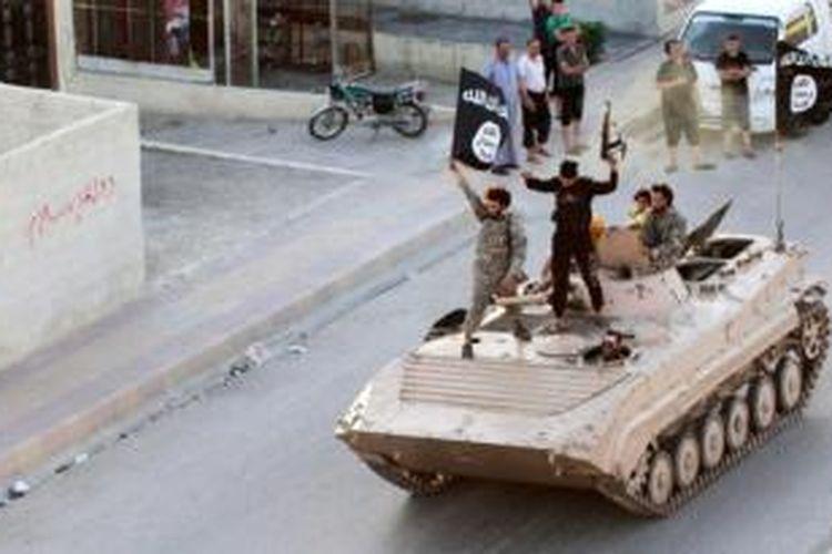 Pejuang ISIS tengah menggelar konvoi di provinsi Raqqa di atas sebuah kendaraan lapis baja.