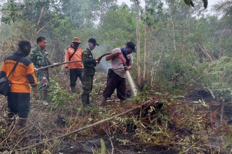 Petugas gabungan dari kepolisian, TNI dan Manggala Agni melakukan pemadaman api karhutla di Kelurahan Teluk Makmur, Kecamatan Medang Kampai, Kota Dumai, Riau, Senin (18/2/2019).
