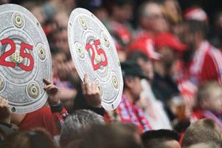 Suporter Bayern Muenchen membentangkan trofi piring salad sebagai simbol juara Bundesliga, Sabtu (23/5/2015).