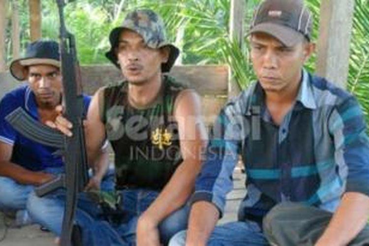 Pimpinan kelompok bersenjata Aceh, Din Minimi (tengah) diapit oleh dua anggotanya di kawasan hutan Aceh Timur, Aceh