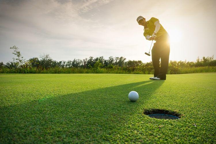 Ilustrasi golf - Seorang pemain golf sedang bermain di padang golf.
