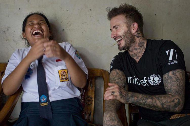 Duta Kehormatan UNICEF David Beckham tertawa bersama Sripun (15) di rumahnya di Semarang, Jawa Tengah, Indonesia, 27 Maret 2018. Sripun diunjuk oleh lingkungannya untuk menjadi agen perubahan dan berpartisipasi dalam program anti-bullying yang diinisiasi UNICEF.